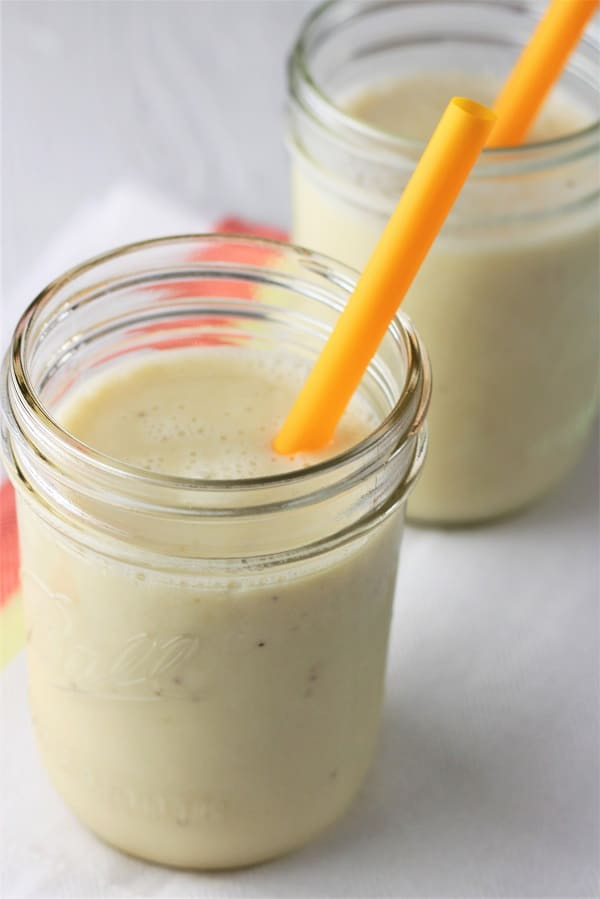 two banana pineapple smoothies in glasses with orange straws on a white napkin with a red and orange stripe