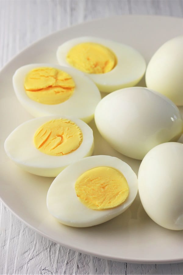 hard-boiled eggs on a plate with a few cut open showing the yolks