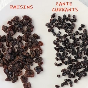 raisins and zante currants shown side-by-side on a white plate