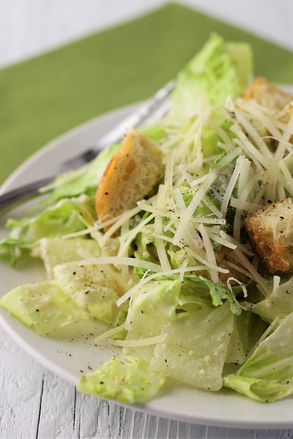 close up of a plate of caesar salad with a fork and green napkin