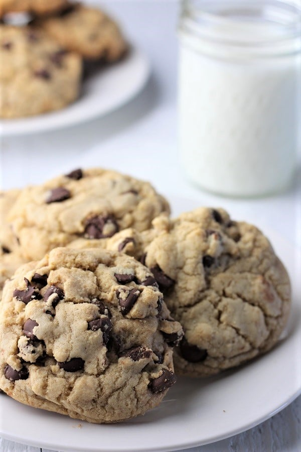 plate of three chocolate chip cookies with a glass of milk and another plate of cookies in the background