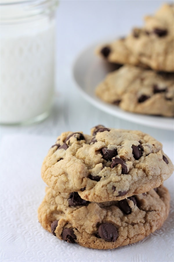two chocolate chip cookies stacked on a plate with a glass of milk and a large plate of cookies in the background