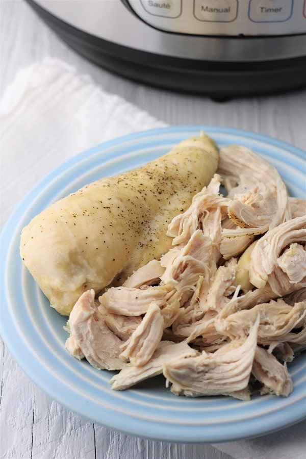whole cooked chicken breast and shredded chicken breast on a white plate on a white napkin with an instant pot in the background