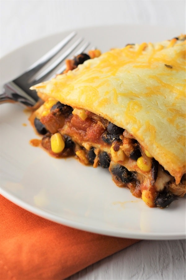 close up of a plain piece of mexican lasagna on a white plate on an orange napkin with a fork