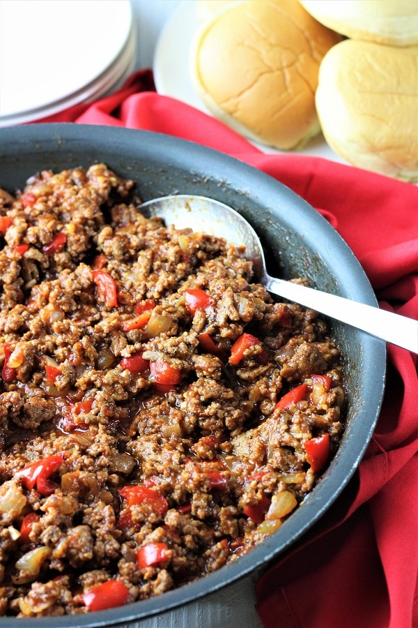 pan of turkey sloppy joes with a serving spoon and plates and buns in the background