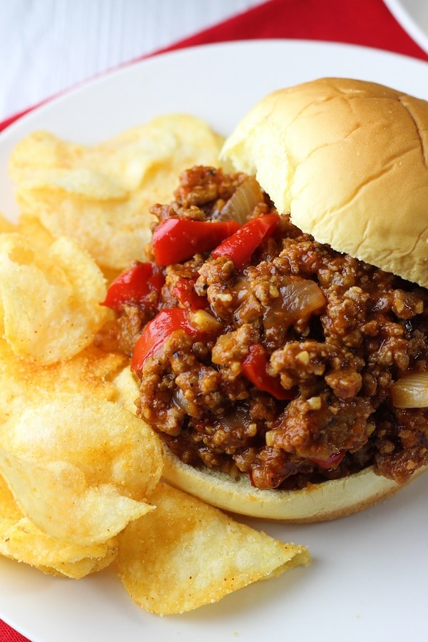 sloppy joe and potato chips on a white plate and red napkin