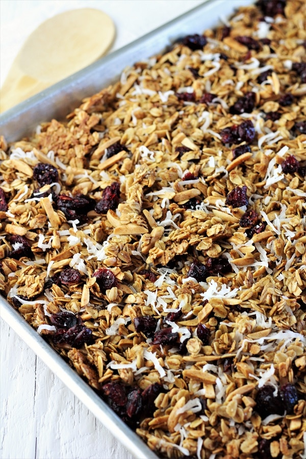 cranberry coconut homemade granola on a sheet pan with a wooden spoon in the background