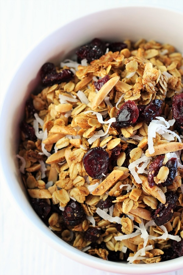 cranberry coconut homemade granola in a white bowl