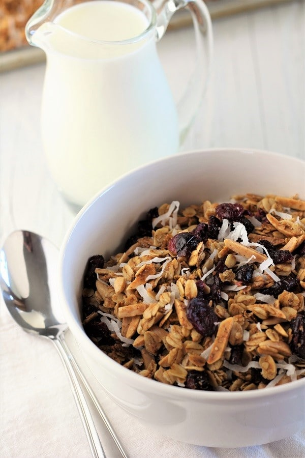 cranberry coconut homemade granola in a white bowl with a pitcher of milk and a spoon next to it