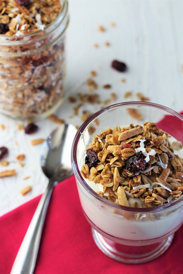 cranberry coconut homemade granola sprinkled on vanilla yogurt in a dessert dish on a magenta napkin with a spoon to the side and a small mason jar of granola in the background with small bits of granola scattered on the table