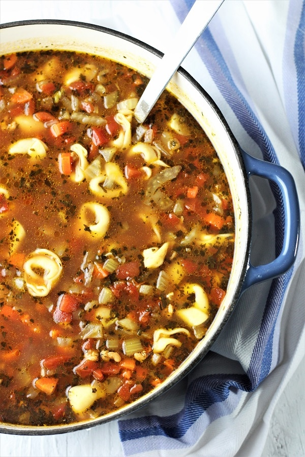 pot of sausage and tortellini soup with a ladle in it and a blue and white napkin on the side
