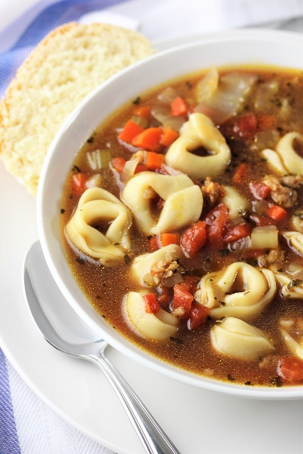bowl of sausage and tortellini soup with a spoon and piece of bread on the side