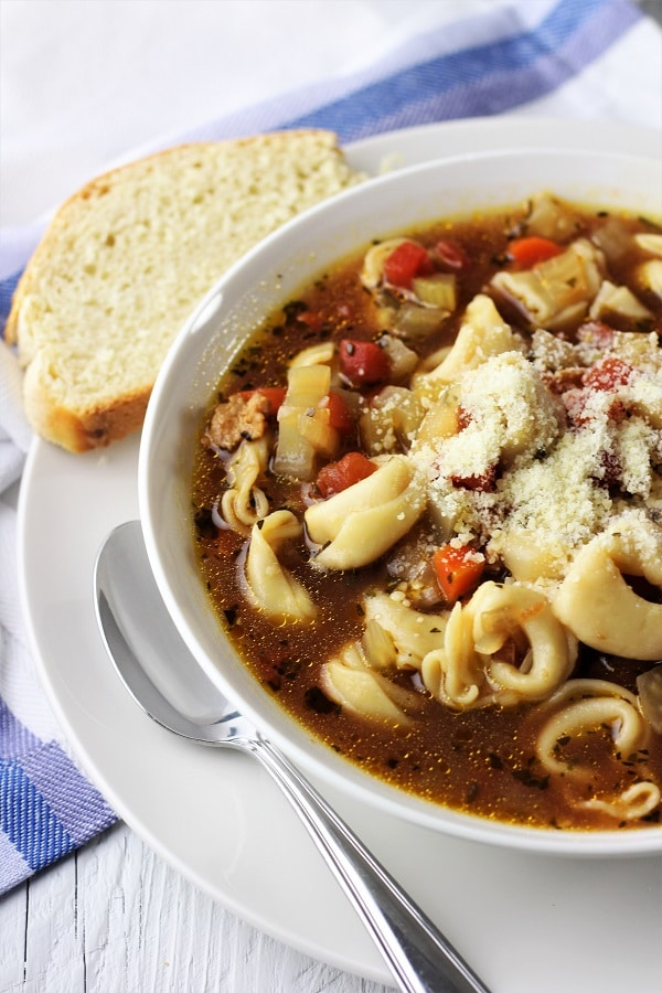 bowl of sausage and tortellini soup with grated Parmesan cheese on top with a spoon and piece of bread on the side and a blue and white napkin