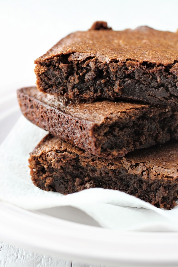 close up of three brownies stacked on a plate
