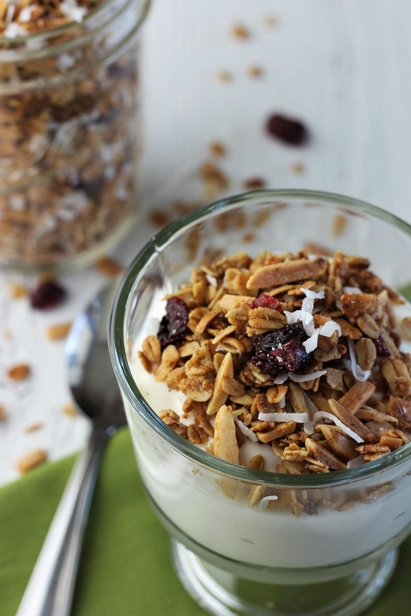 bowl of yogurt with granola on top on a green napkin with a spoon on the side and a mason jar of granola in the background and some granola scattered around