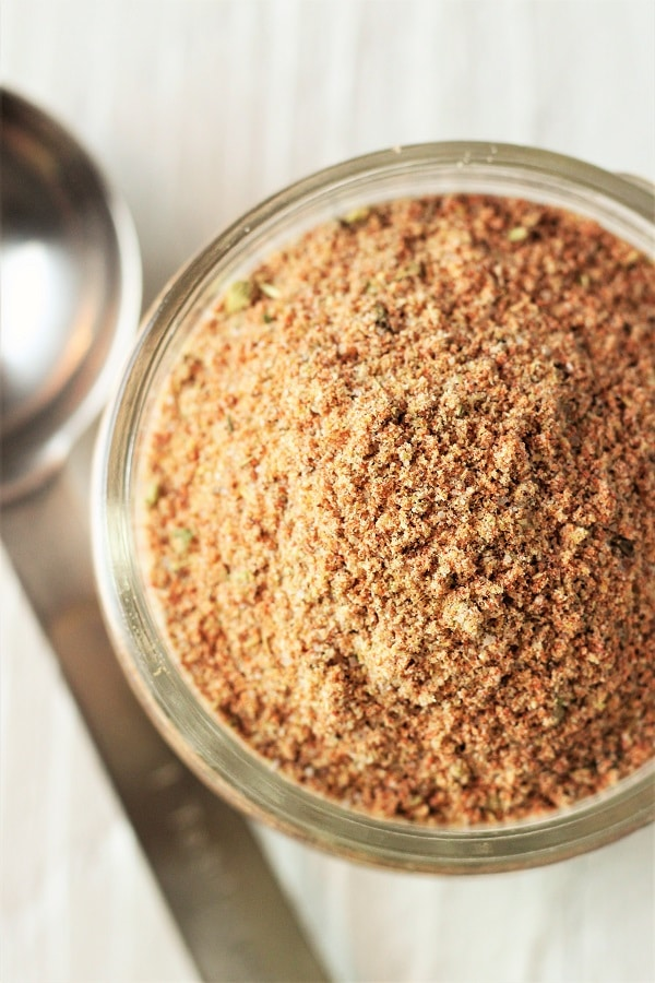 jar of homemade taco seasoning with a measuring spoon next to it