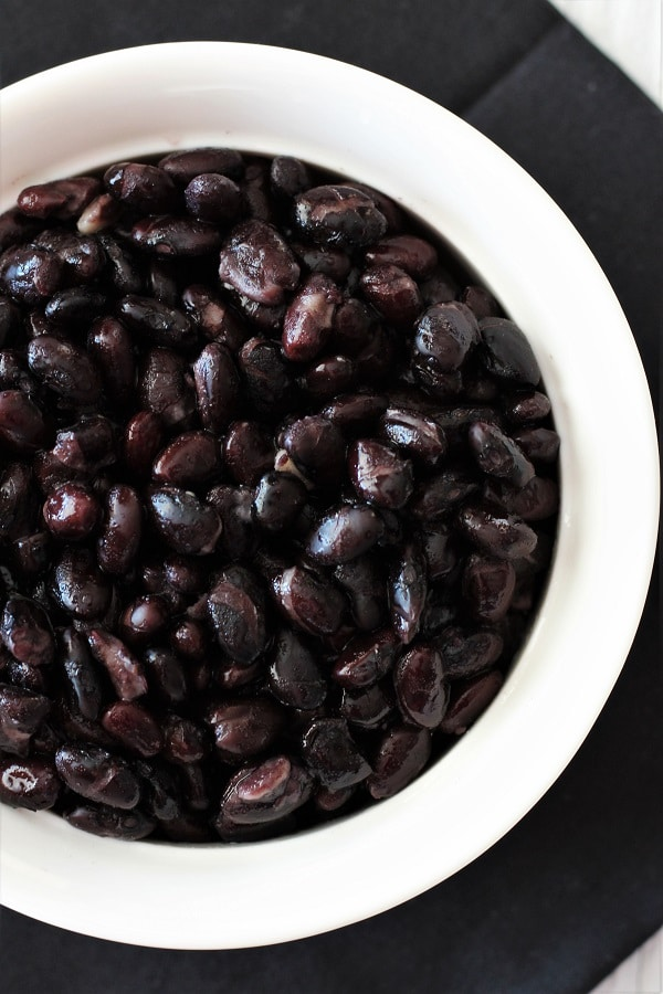 white bowl of cooked black beans on a black napkin