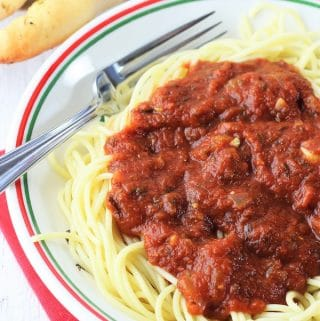 bowl of spaghetti and sauce on a red napkin with a fork and breadsticks in the background