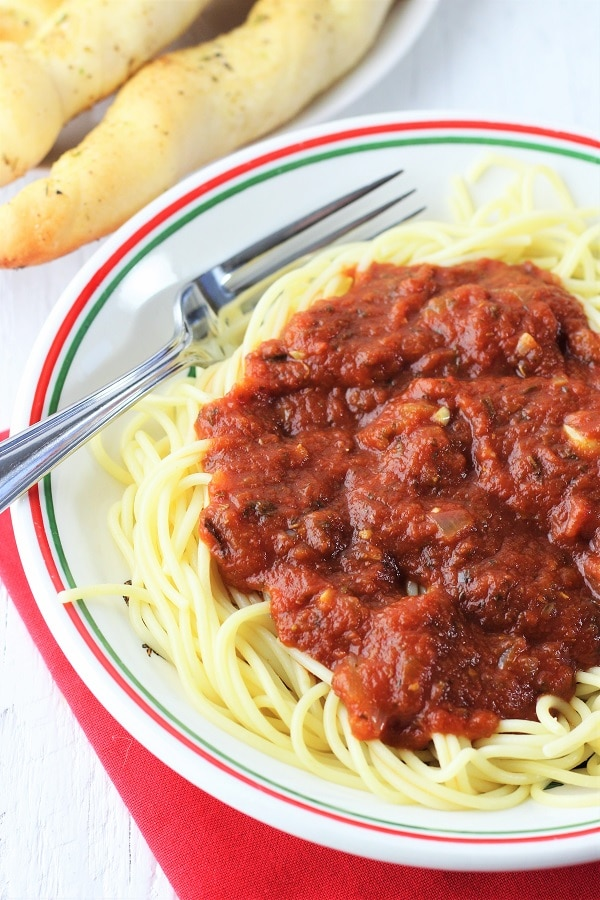 bowl of spaghetti and sauce with a fork on a red napkin and breadsticks on the side