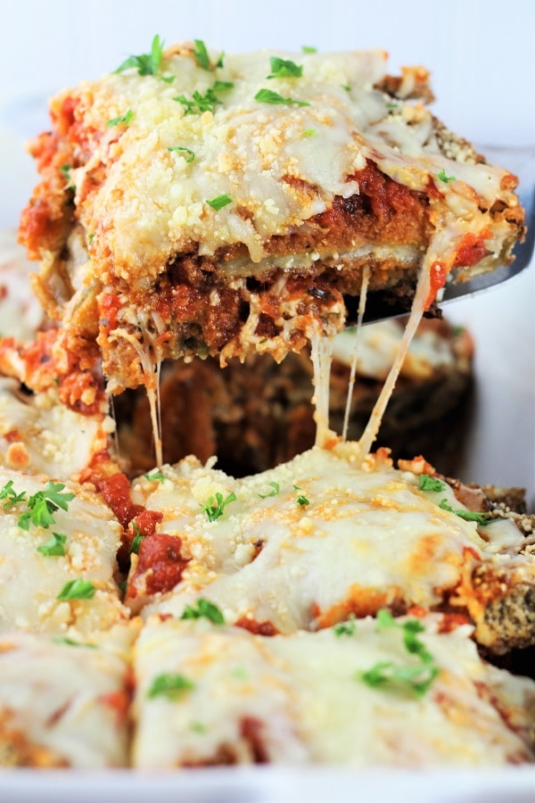 close up of a piece of baked eggplant parmesan being lifted out of a baking dish