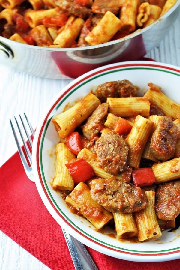 bowl of sausage and peppers pasta on a red napkin with a fork on the side and a pan of pasta in the background