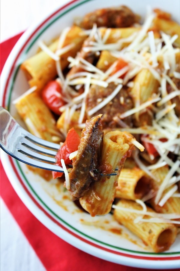 forkful of rigatoni, sausage and pepper being taken out of a bowl of sausage and peppers pasta