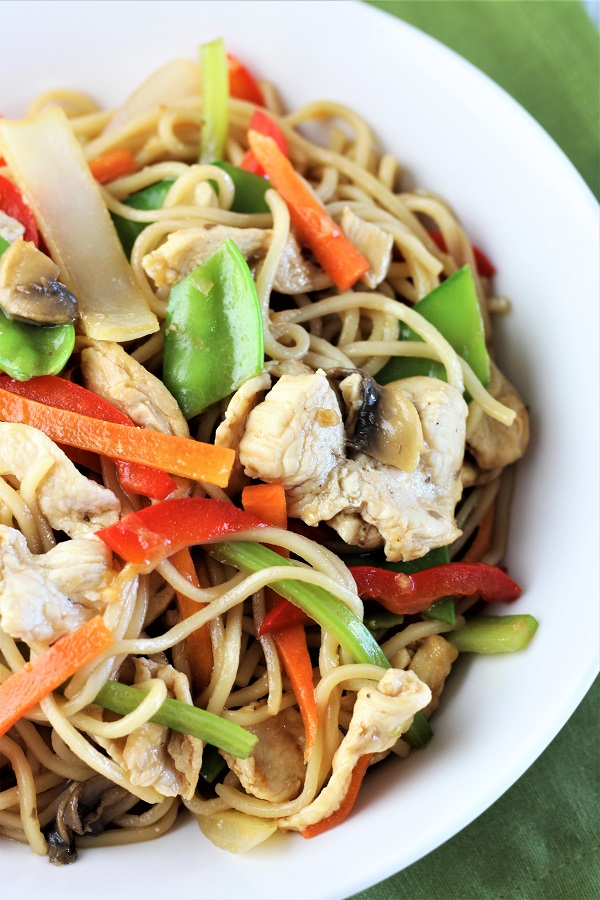 bowl of chicken and veggie lo mein on a green napkin