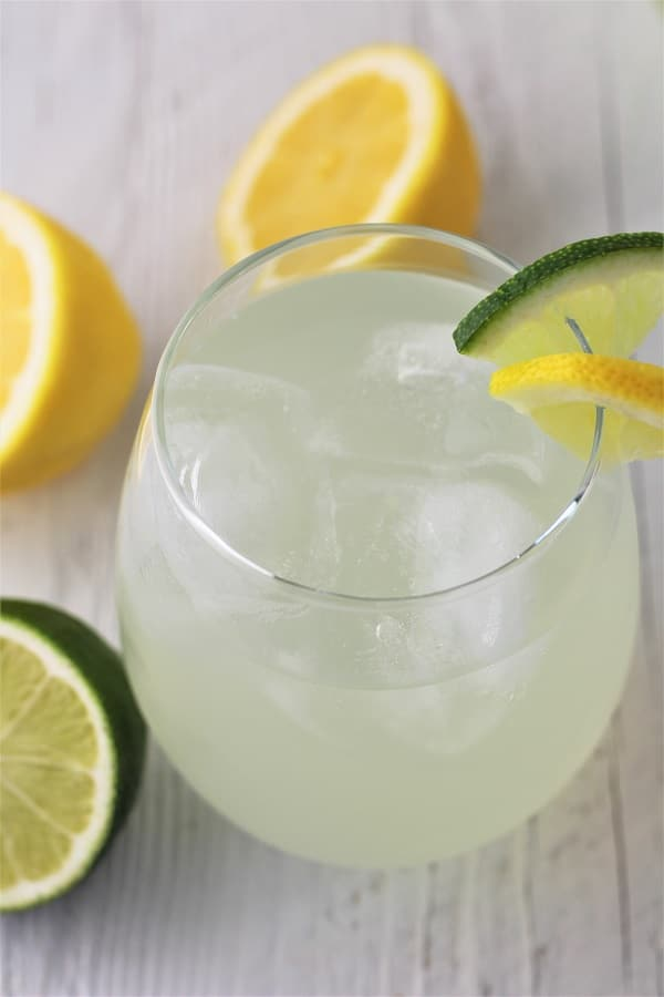 glass of lime lemonade with ice and lemon and lime wedges and lemons and limes scattered in the background