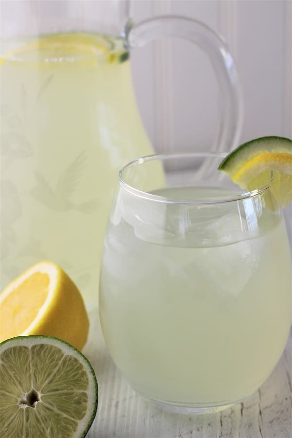 glass of lime lemonade with ice and lime and lemon wedges, lime and lemon halves on the side, and a pitcher of lime lemonade in the background