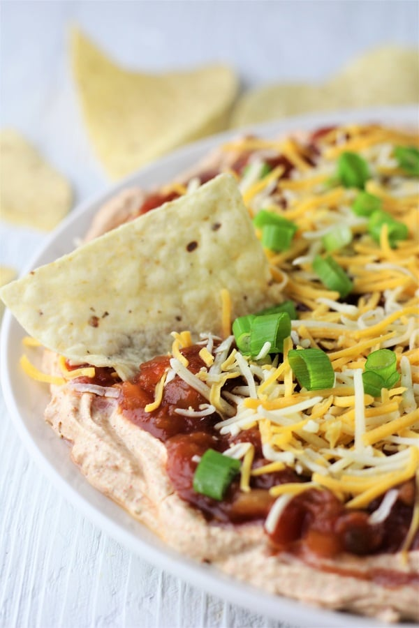 dish of easy taco dip with a tortilla chip in it and tortilla chips in the background