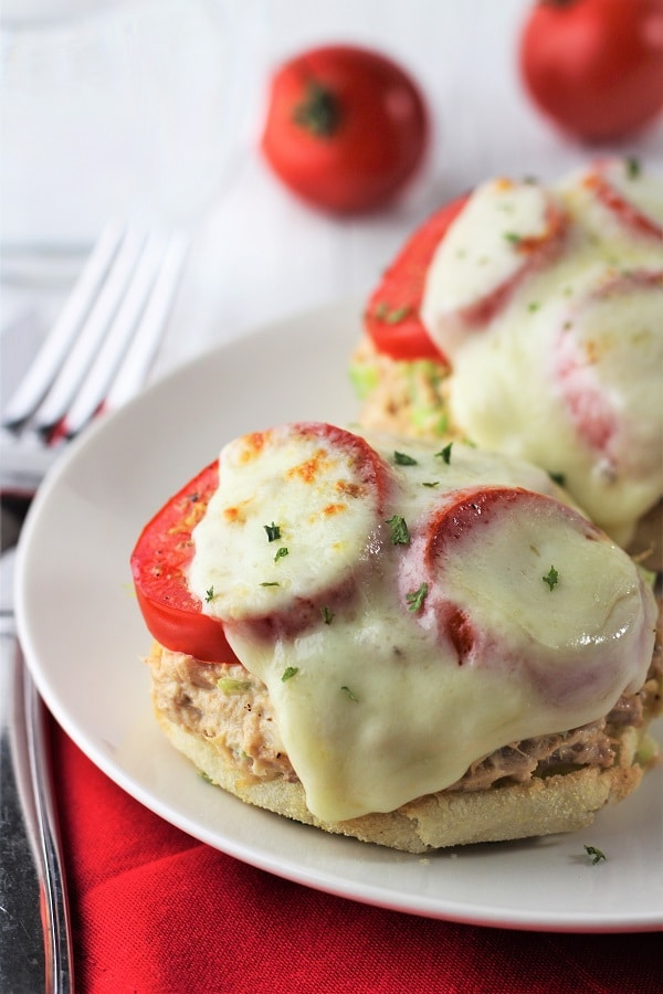 english muffin tuna melts on a white plate on a red napkin with a knife and fork on the side and a glass of water and tomatoes in the background