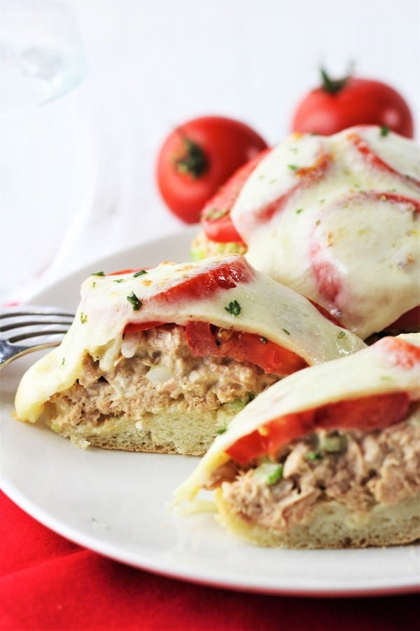English muffin tuna melt cut in half on a plate with a whole tuna melt behind it and some tomatoes in the background