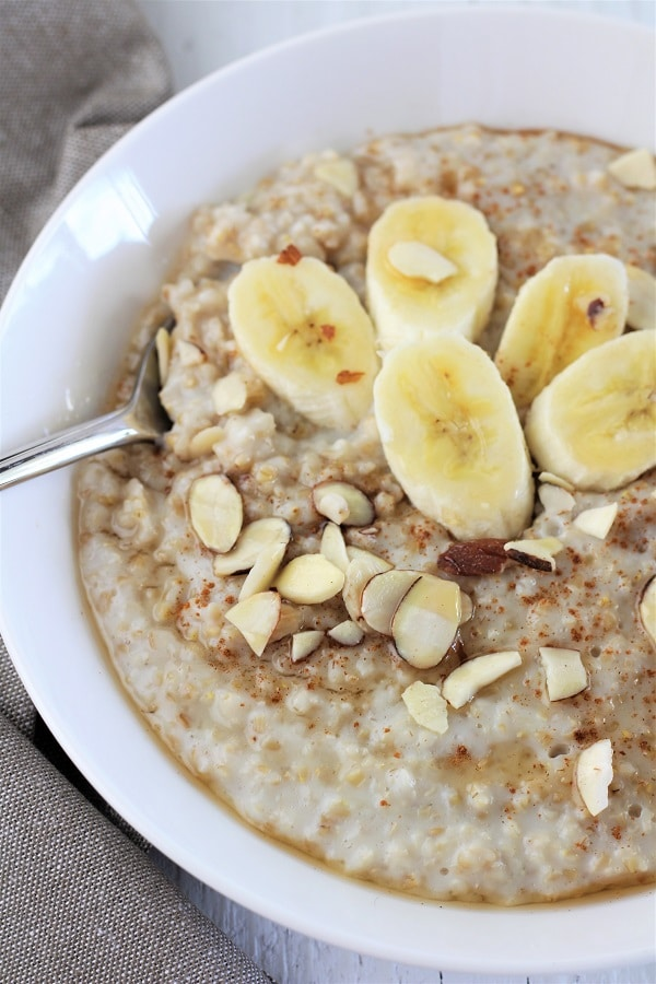 bowl of steel cut oats topped with banana, cinnamon, maple syrup, and almonds