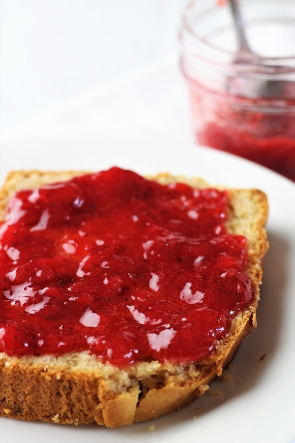 strawberry refrigerator jam spread on a slice of peanut butter bread with a jar of jam in the background