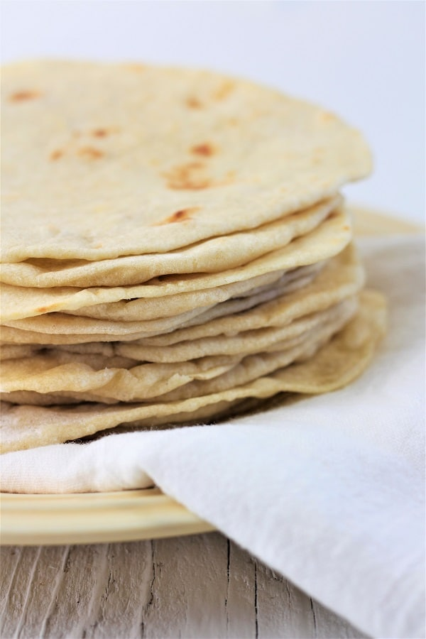 stack of homemade flour tortillas on a plate