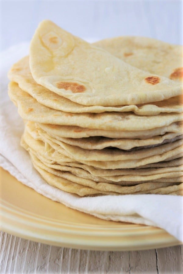 stack of homemade flour tortillas on a plate with the top one folded over