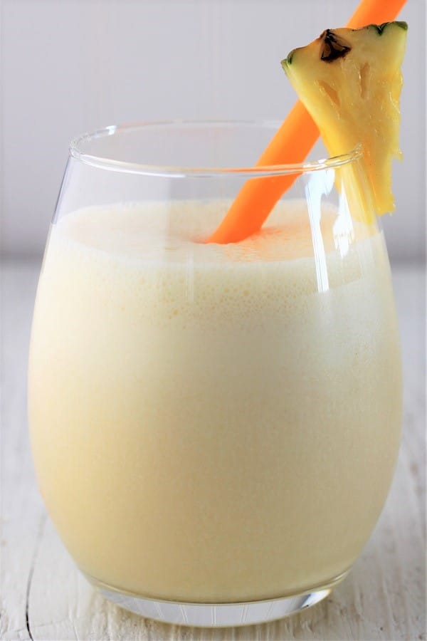 glass of pineapple julius with an orange straw and a piece of pineapple on the glass