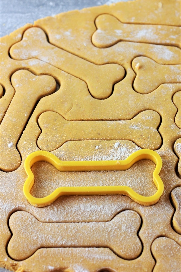 bone shapes being cut out of dough with a bone-shaped cookie cutter