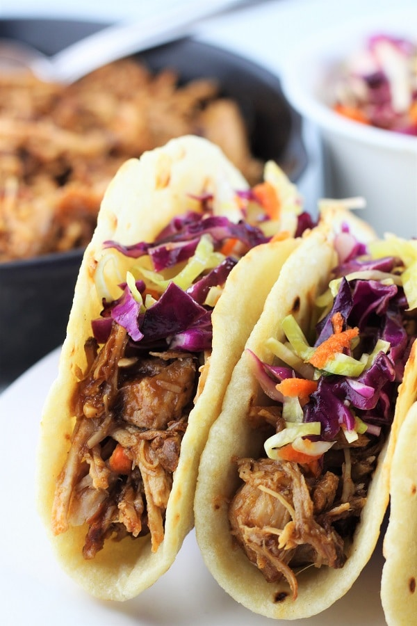 two bbq pulled pork tacos on a plate with a pan of pulled pork and a bowl of coleslaw in the background