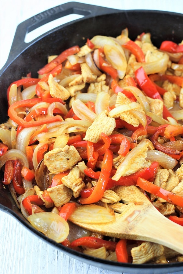 cast iron skillet full of skillet chicken fajitas mixture of chicken, peppers, and onions