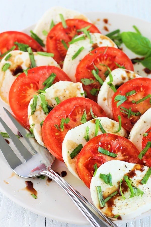 plate of Caprese salad with balsamic drizzle with a serving fork
