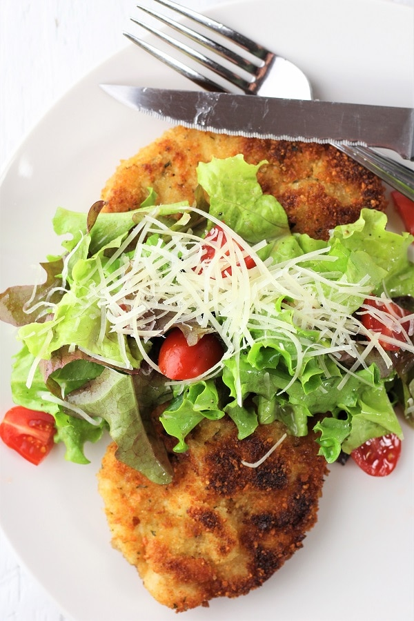 chicken milanese with mesclun salad topped with shredded parmesan cheese on a white plate with a fork and knife