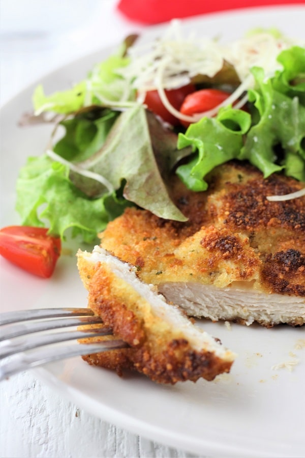 chicken milanese with mesclun salad with a piece of the chicken cut off and on a fork