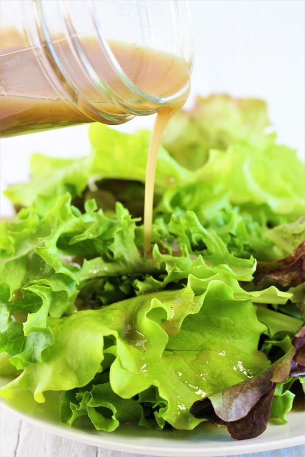 Maple Balsamic Vinaigrette being poured onto a salad from a jar