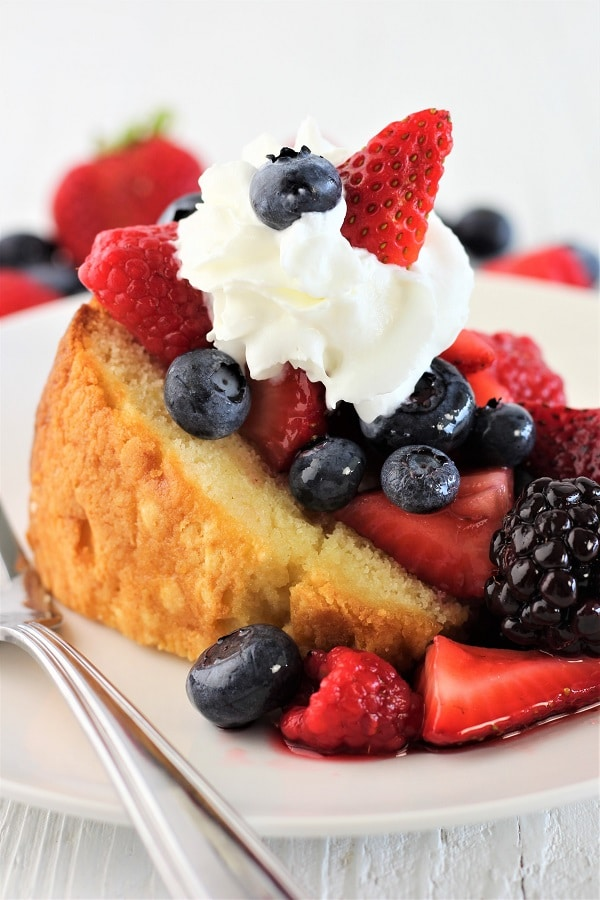 pound cake with marsala mixed berries and whipped cream on a plate with a fork