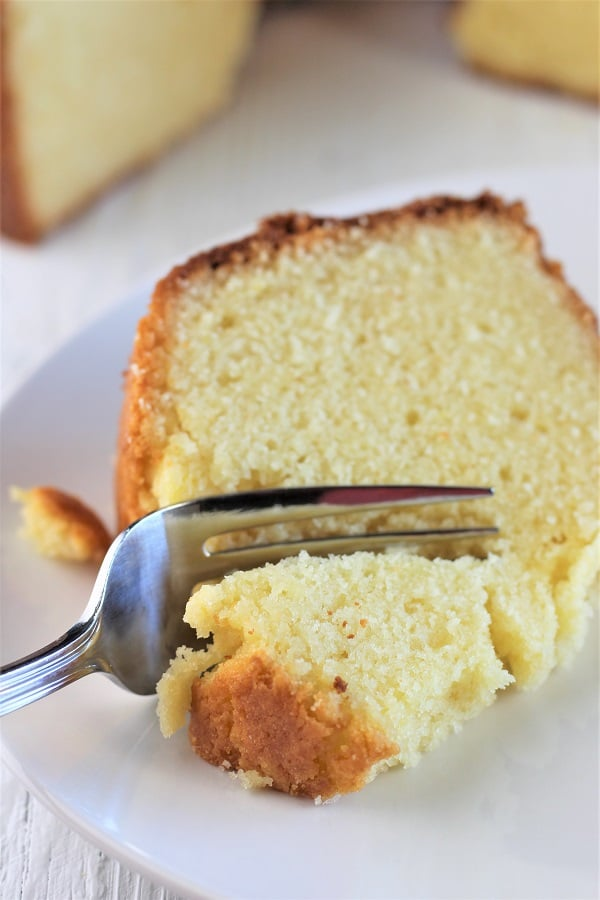 piece of vanilla almond pound cake on a plate with a forkful being taken out