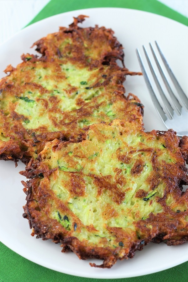 two zucchini potato pancakes with a fork on a white plate on a green napkin