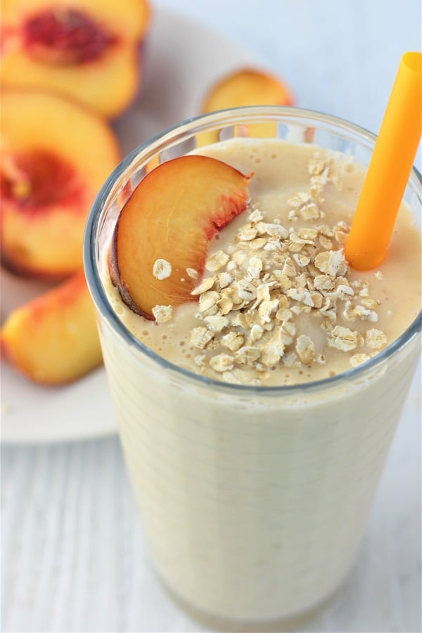 peach and oat smoothie with an orange straw and a peach slice and oats on the top and a plate of halved peaches in the background