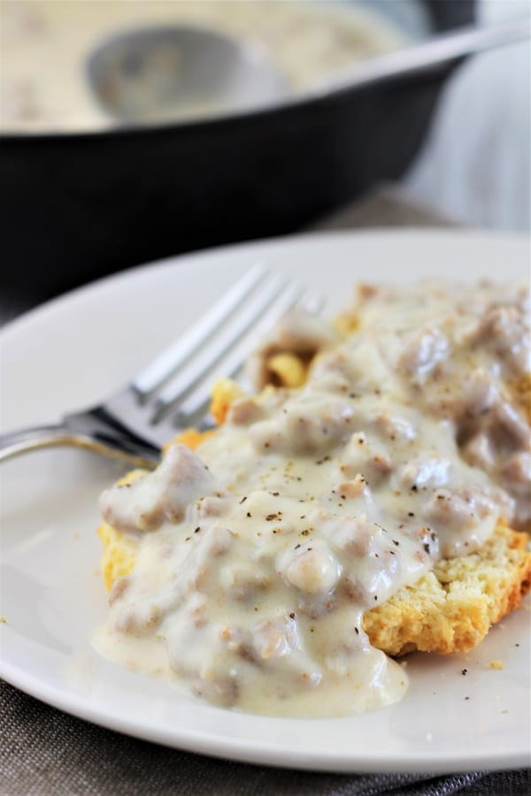 homemade sausage gravy over biscuits on a white plate with a fork and a pan of sausage gravy in the background