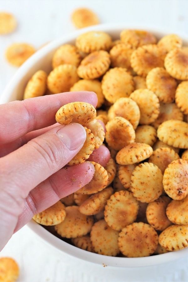 hand grabbing some crackers out of a bowl of cajun spiced oyster crackers